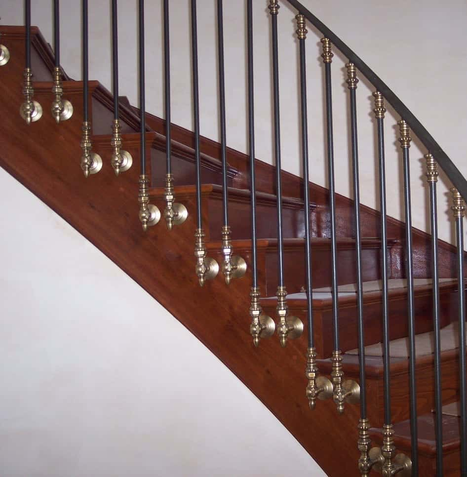 Side mount baluster bracket in brass with black spindle on dark wood stairs