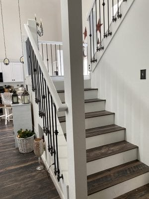 Side mount baluster bracket with black spindle on white painted wood stairs, side view