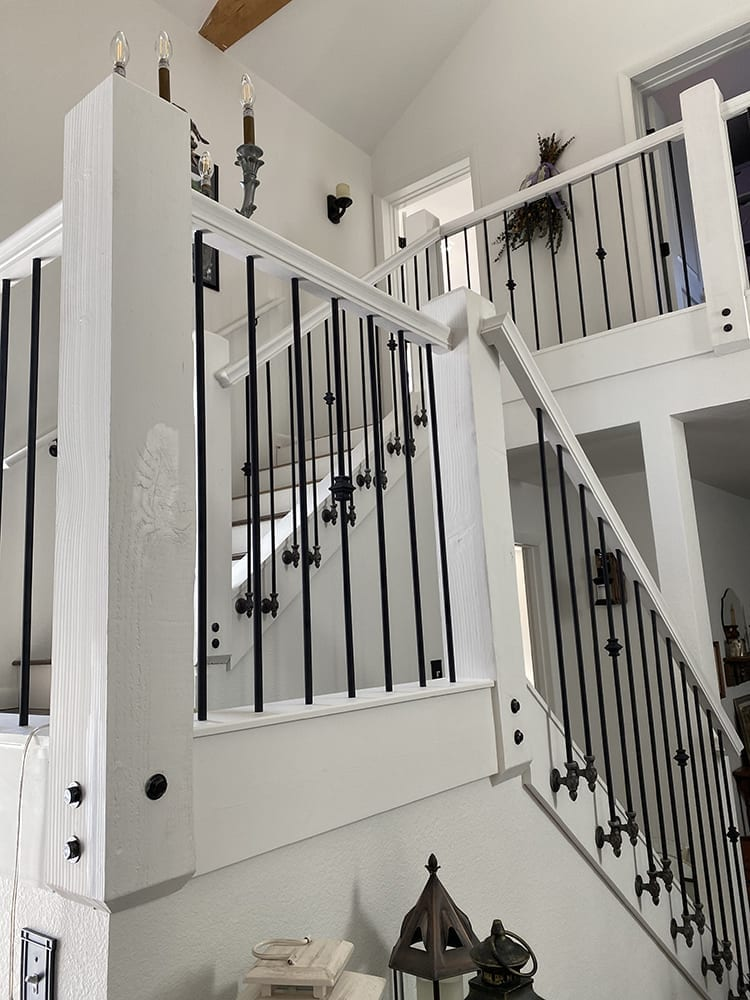 Side mount baluster bracket with black spindle on white painted wood stairs