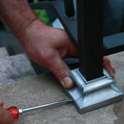Second installation step for split shoe, covering mismatched caulking around square post. Use screwdriver to fasten the two parts around a post