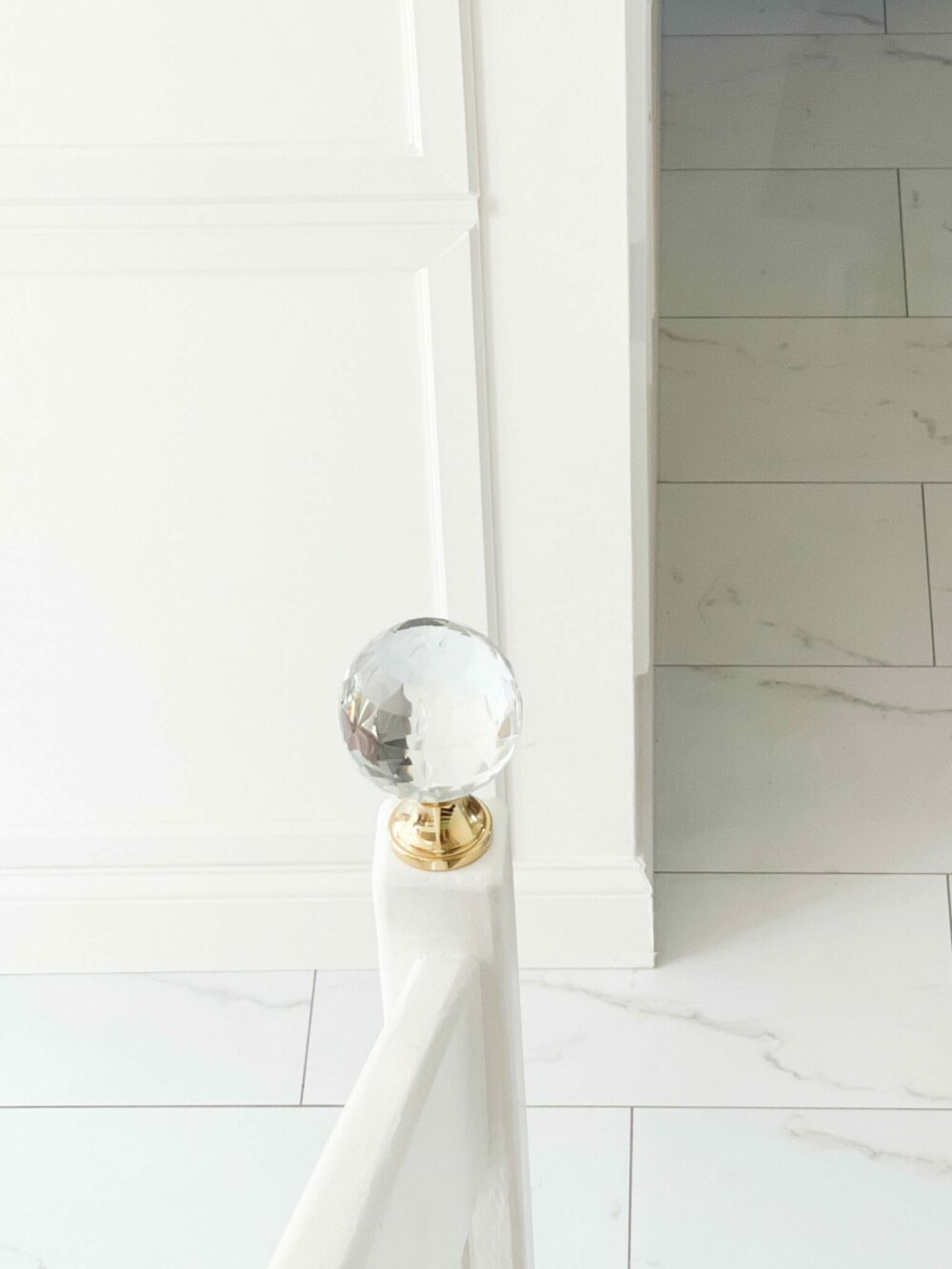 Large crystal finial on brass base, mounted on white staircase railing newel post.