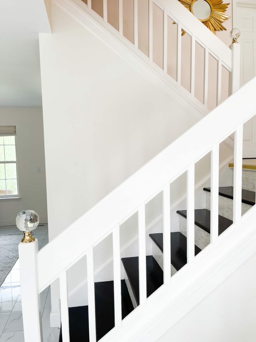 Two large crystal finials on brass base, mounted on white staircase railing newel posts.
